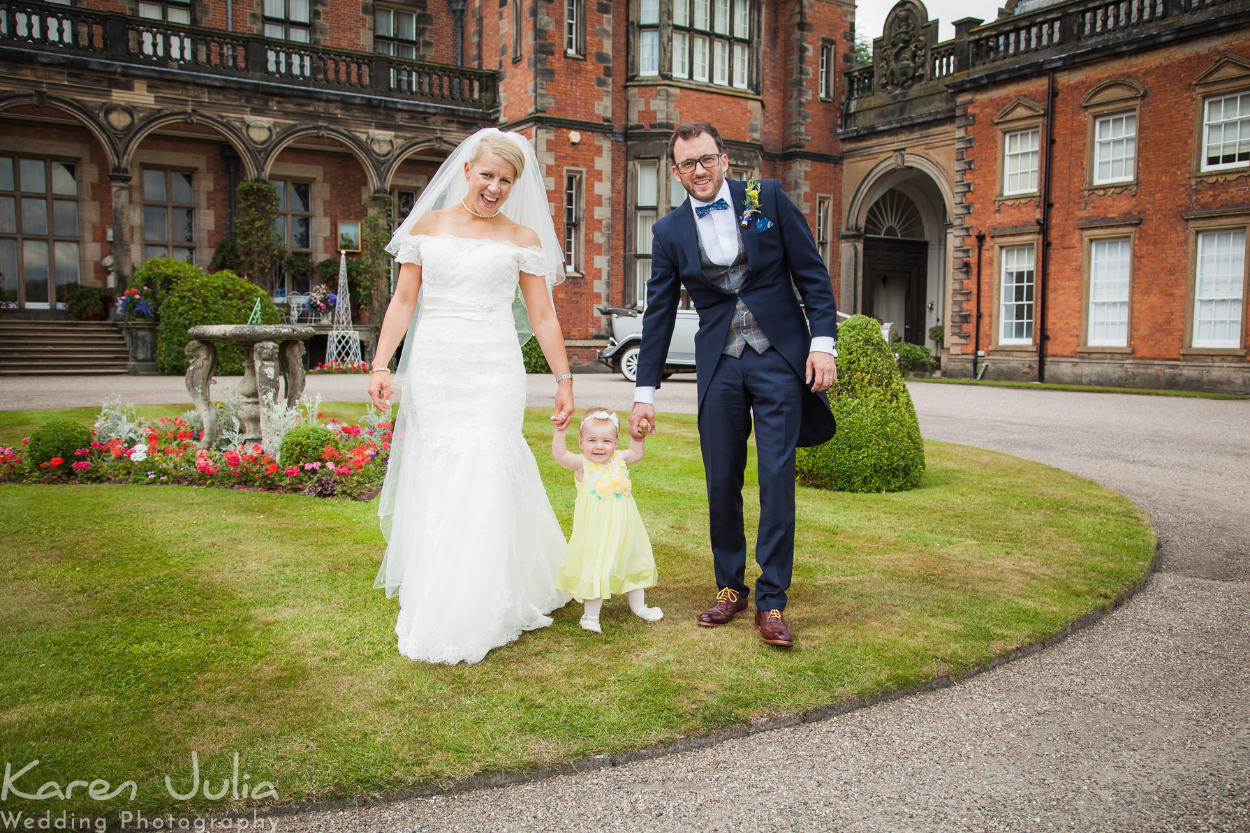 bride and groom with young child on wedding day